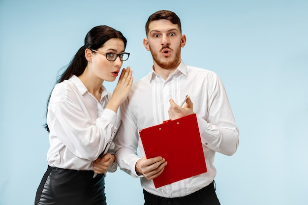 De verbaasde zaken man en vrouw lachend op een blauwe studio achtergrond