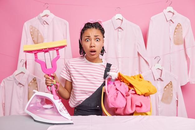 De verbijsterde, drukke etnische huisvrouw draagt een wasmand en houdt een dweil tegen gestreken hemden.