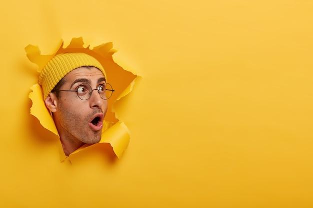 De verbijsterde man kijkt met grote verbazing of angst opzij, opent zijn mond wijd, draagt een hoed en een ronde bril