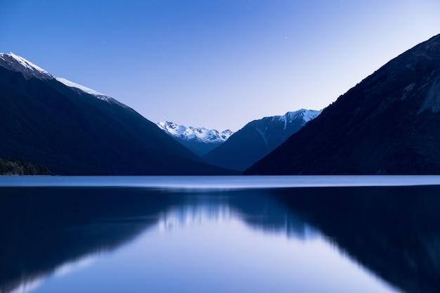 De verbluffende weerspiegeling van de berg van de alpen op het meer na zonsondergang. st arnaud, nelson lakes national park.