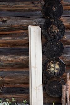 De verduisterde muur van een traditioneel houten huis vers bord dat tegen een houten muur staat