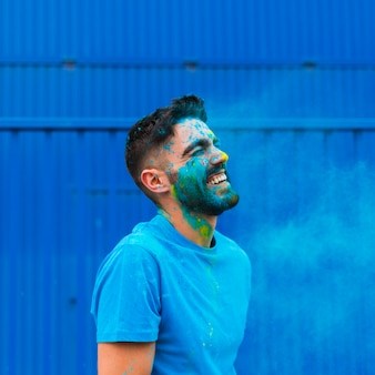 De verf bevlekte jonge mens die op holi-festival lacht