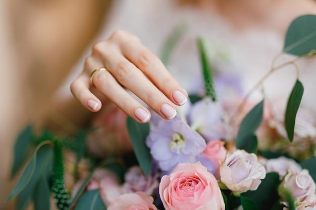 De verfijnde hand van de bruid met een trouwring raakt zachtjes de bloemen van het bruidsboeket