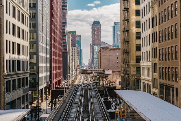 De verhoogde treinsporen lopen boven de spoorwegsporen tussen het gebouw bij de lijnlijn in chicago, illinois, de vs