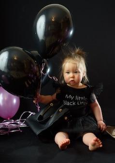 De verjaardag van het eerste jaar babymeisje. ballons en vakantie binnenshuis. verjaardag van het kind. mooi meisje in haar eerste zwarte jurk