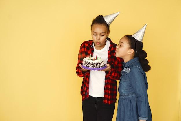 De verjaardag van kleine meisjes die op gele muur wordt geïsoleerd. kinderen die cake houden.