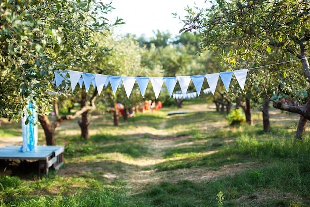 De verjaardagsdecoratie die van vlaggen op boomtak hangen in tuin. tuinfeest decoratie. bruiloft decor.