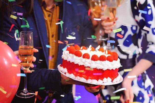 De verjaardagstaart met kaarsen sluit omhoog op de achtergrond van het vrolijke gezelschap van mijn beste vrienden
