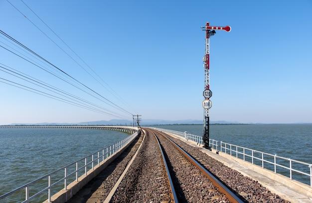 De verkeerslichtpaal in de stoppositie van het spoorwegsignalisatiesysteem op de betonnen brug