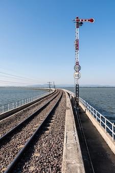 De verkeerslichtpaal in het stopsignaal van het spoorwegsignaleringssysteem op de gebogen betonnen brug