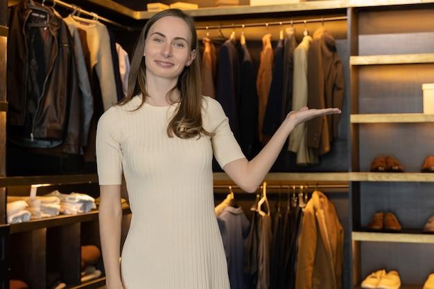 De verkoopster lacht en laat de kleren in de kostuumwinkel zien en praat tegen de camera