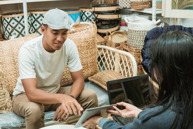 De verkoper deelt een digitale tablet met een ambachtelijke koper om in een ambachtelijke werkplaats haar catalogus van handwerkwinkel te bekijken