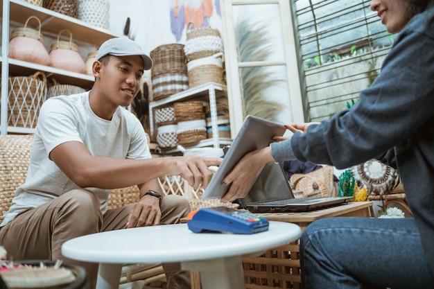 De verkoper en de koper gebruiken tabellen en gebruiken machines voor het vastleggen van elektronische gegevens als betalingsmogelijkheden in de ambachtswinkel