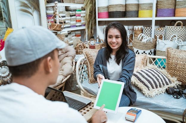 De verkoper gebruikt een tablet en gebruikt machines voor het vastleggen van elektronische gegevens als betalingsfaciliteiten bij een ambachtelijke winkel