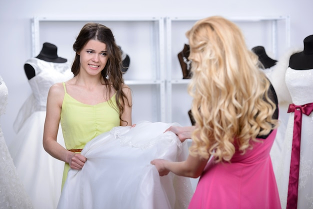 De verkoper geeft de blonde een nieuwe witte jurk.