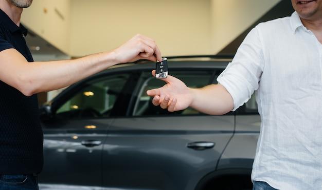 De verkoper geeft de sleutels van een nieuwe auto aan een jong gezin. een nieuwe auto kopen.