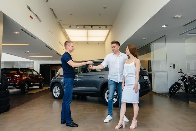 De verkoper geeft de sleutels van een nieuwe auto aan een jong gezin