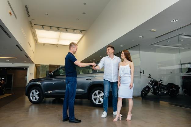 De verkoper geeft de sleutels van een nieuwe auto door aan een jong gezin. een nieuwe auto kopen.