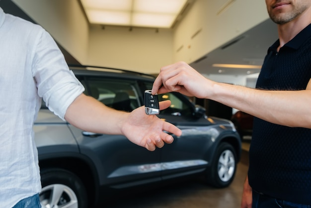 De verkoper geeft de sleutels van een nieuwe auto door aan een jong gezin