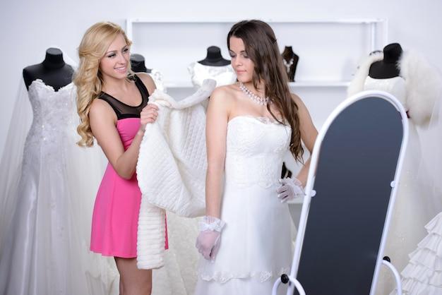 De verkoper helpt de koper om een trouwjurk te kiezen.