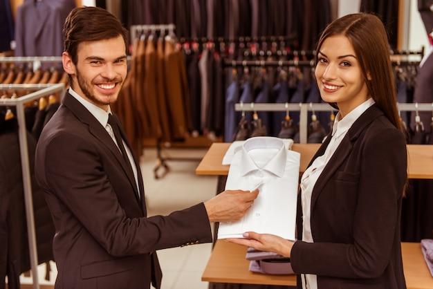 De verkoper hielp de man om het juiste shirt te kiezen.