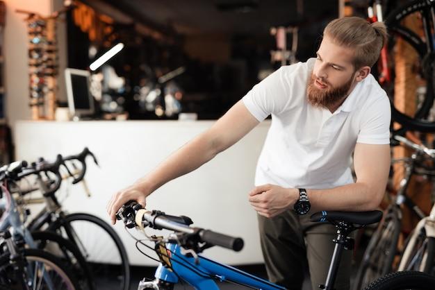 De verkoper in de fietsenwinkel houdt het fietsstuur vast.