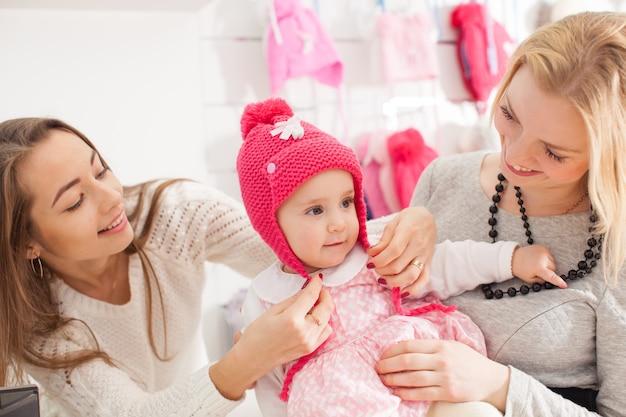 De verkoper laat een roze meisjeshoed met pompon zien om aankopen te selecteren