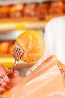 De verkoper pakt brood in bakkerij in
