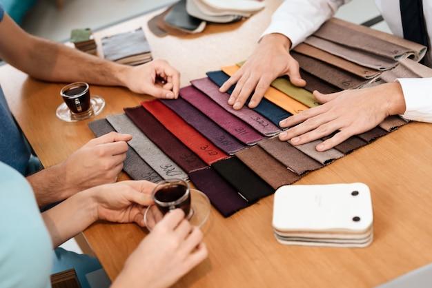 De verkoper toont voorbeelden van materialen voor meubels.