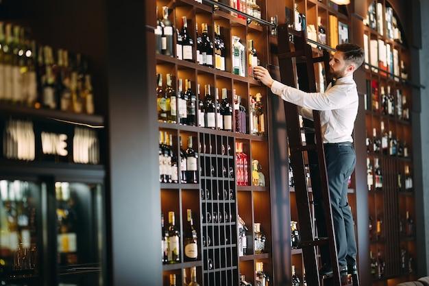 De verkoper van alcoholische dranken sorteert flessen die op de ladder staan