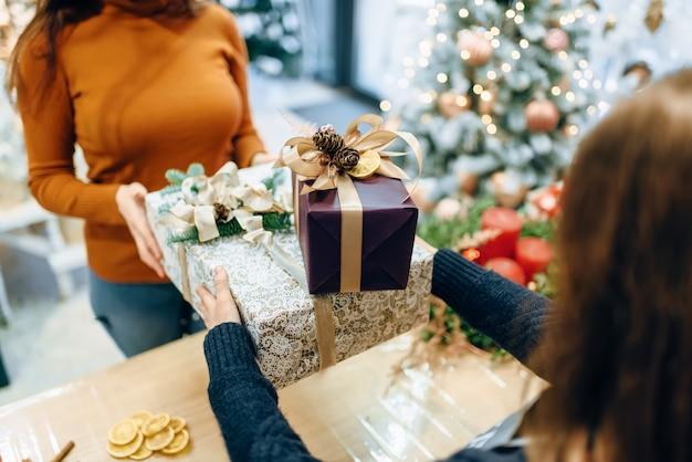 De verkoper van de inpakservice geeft aan de klant een kerstgeschenkdoos.