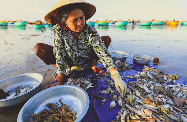 De verkoper verzamelt vissen in het beroemde vissersdorp in mui ne, vietnam
