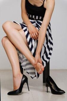 De vermoeide dame geeft zich voetmassage zittend op een stoel. vermoeide vrouwelijke benen.