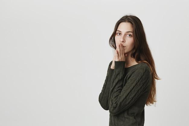 De vermoeide en bezorgde jonge vrouw die smeekt, houdt handen dichtbij hoopvolle lippen