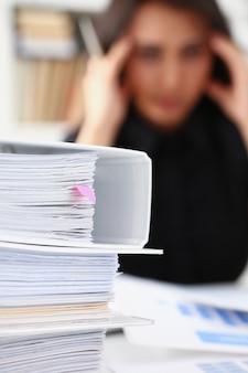 De vermoeide en uitgeputte vrouw bekijkt documenten die haar hoofd met haar handen steunen