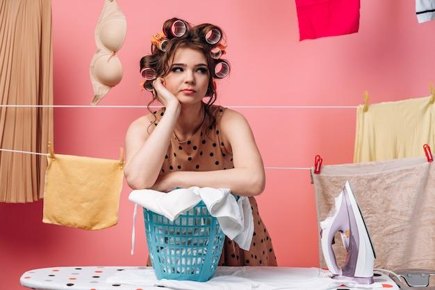 De vermoeide huisvrouw leunde op een mand met kleren en keek weg. touw met kleren op een roze achtergrond.