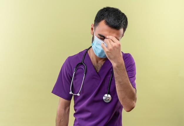 De vermoeide jonge mannelijke arts die purpere chirurgenkleding en het medische masker van de stethoscoop draagt, legde zijn hand op voorhoofd op geïsoleerde groene muur