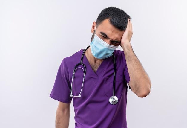De vermoeide jonge mannelijke arts die purpere chirurgkleding en het medische masker van de stethoscoop draagt legde zijn hand op hoofd op geïsoleerd wit