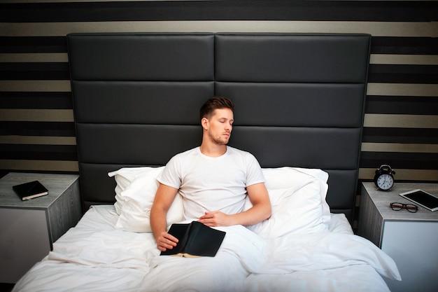 De vermoeide jonge mensenslaap in slaapkamer in het zitten stelt. hij houdt een zwart boek op zijn knieën. man is bedekt met witte deken.