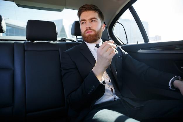 De vermoeide jonge oogglazen van de zakenmanholding en het rusten