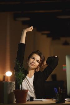De vermoeide jonge zitting van de vrouwenontwerper in bureau bij nacht
