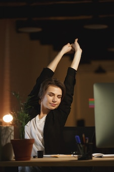 De vermoeide jonge zitting van de vrouwenontwerper in bureau
