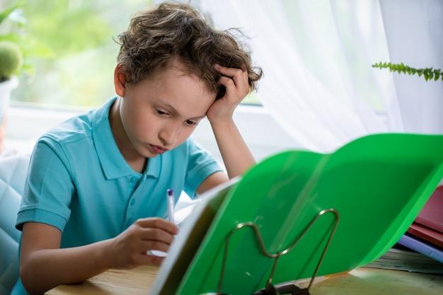 De vermoeide jongen legt zijn hand onder zijn hoofd en kijkt weg, zittend aan een bureau en een les