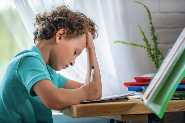 De vermoeide jongen legt zijn hand op hoofd en kijkt weg, zittend aan bureau en lesend