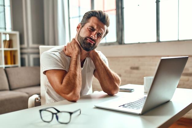 De vermoeide man legde zijn handen in zijn nek, van pijn. freelance, thuiswerken. een man werkt op een laptop.