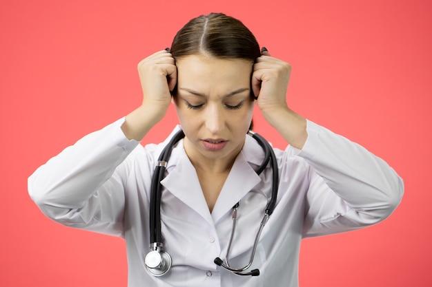 De vermoeide mooie arts houdt handen bij tempels, voelt hoofdpijn, overwerkte verpleegster