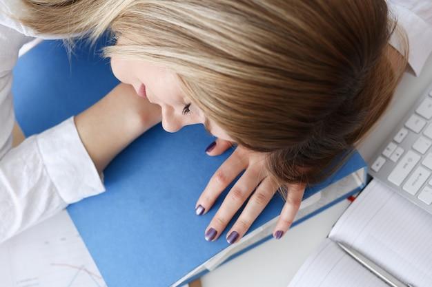 De vermoeide onderneemster bij werkruimte in bureau neemt dutje