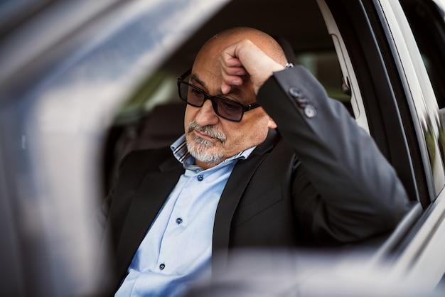 De vermoeide rijpe zakenman zit binnen van zijn auto en denkt over zijn baan na.