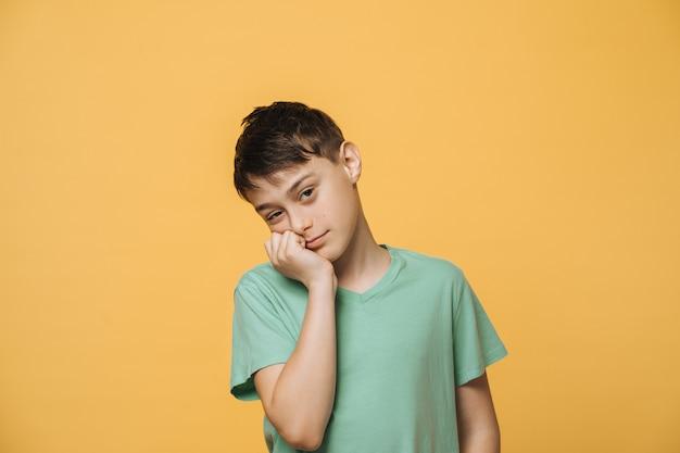 De vermoeide schooljongen met bruine ogen gekleed in een groen t-shirt, steunt zijn hoofd met de hand, heeft weinig energie na veel oefeningen. onderwijs en jeugdconcept.