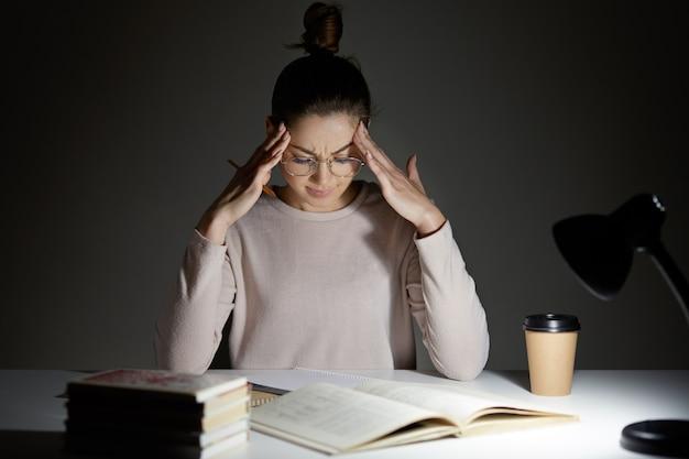 De vermoeide stressvolle vrouw houdt handen op het hoofd
